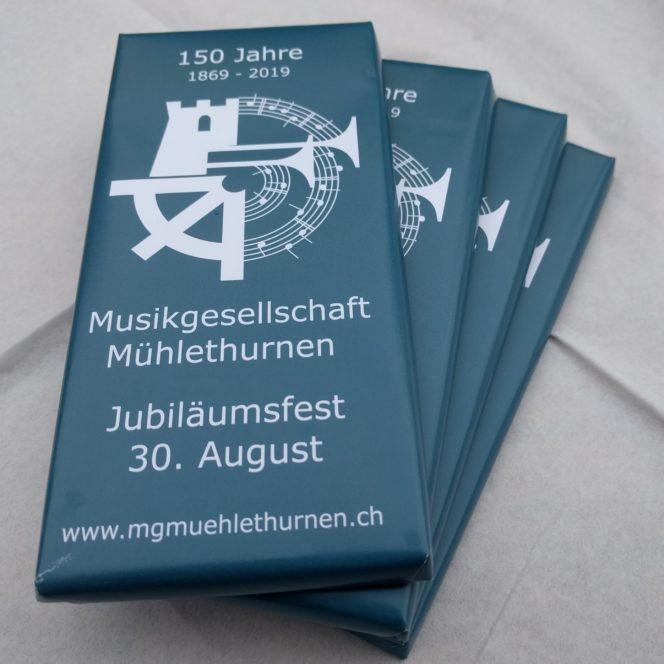 100g Schokoladetafel mit Türkis Grundierung und weissem Aufdruck: 150 Jahre 1869-2019 Logo MGM Musikgesellschaft Mühlethurnen Jubiläumsfest 30. August www.mgmuehlethurnen.ch